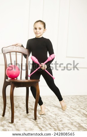 beautiful sport training rhythmic gymnastic girl with Rhythmic pink clubs doing professional exercises in white training room. standing near wooden chair  - stock photo
