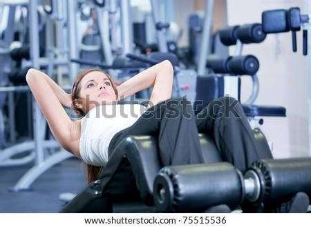 Beautiful sport woman doing press fitness exercise at sport gym - stock photo