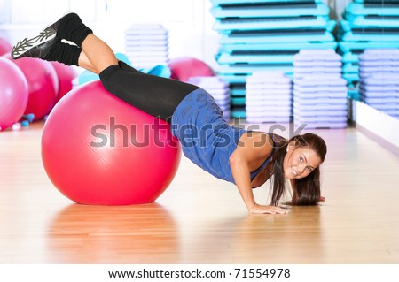 Beautiful sport woman doing stretching fitness exercise at sport gym. Ball - stock photo