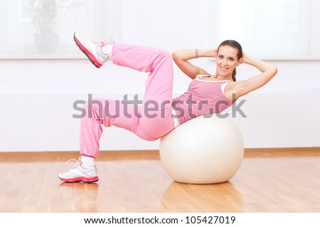 Beautiful sport woman doing stretching fitness exercise on ball at sport gym - stock photo