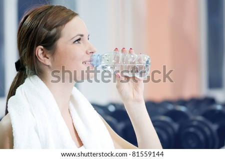 Beautiful sport woman drink water after after fitness exercise at sport gym - stock photo