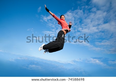 Beautiful sport woman in urban sportswear jumping and fly over blue sky with clouds