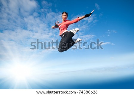 Beautiful sport woman in urban sportswear jumping and fly over blue sky with clouds and sun beam