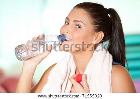 Beautiful sport woman with towel drink cold fresh mineral water after sport train. Thirst! - stock photo