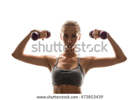 Beautiful sportive girl training with dumbbells over white background.