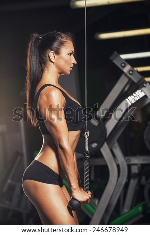 beautiful sports fitness girl  in the gym, triceps - stock photo