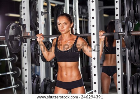 beautiful sports fitness girl with a barbell in the gym, crouches - stock photo