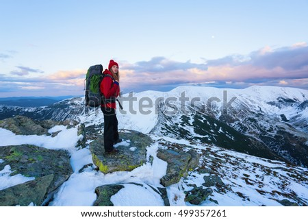 Beautiful sports girl with a red hat and jacket  walks through  the fields and meadows covered with snow hidden away in the high mountains and looking by the surrounding landscape and incredible sky.