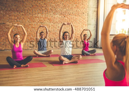 Beautiful sports people are sitting in lotus position and smiling while doing yoga with a trainer in modern fitness hall
