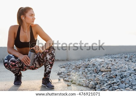 Beautiful sportswoman with bottle of water resting after workout on the street at sunset