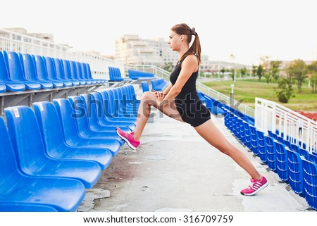 Beautiful sporty athletic girl in shorts and sleeveless shirt stretching between blue seats on a stadium during evening run outdoors at university campus stadium - stock photo