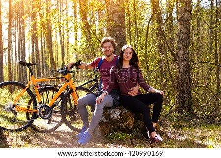 Beautiful sporty couple relaxing after bicycle riding in a forest.