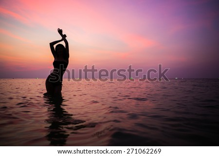 Beautiful sporty feminine silhouette. Evening swimming. Dancing in the fire water - stock photo