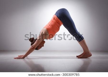 Beautiful sporty fit yogini woman practices yoga asana adhomukha svanasana - downward facing dog pose in studio - stock photo