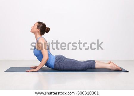Beautiful sporty fit yogini woman practices yoga asana bhujangasana - cobra pose in studio - stock photo