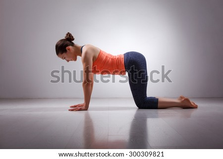 Beautiful sporty fit yogini woman practices yoga asana bitilasana - cow pose gentle warm up for spine (also called cat-cow pose) in studio - stock photo