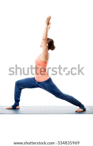 Beautiful sporty fit yogini woman practices yoga asana Virabhadrasana 1 - warrior pose 1 isolated