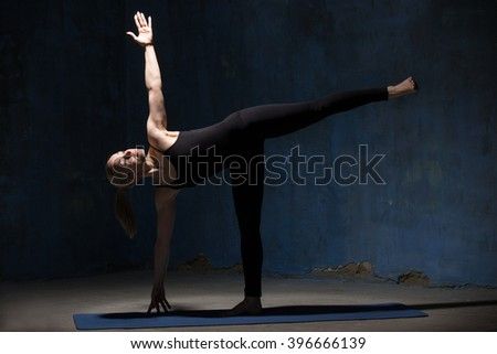 Beautiful sporty fit young woman in black sportswear working out indoors against grunge dark blue wall. Model standing in Ardha Chandrasana posture, Half Moon Pose. Full length. - stock photo