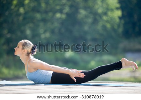 Beautiful sporty fit young woman in sportswear working out outdoors in park on summer day, doing Salabhasana, Locust Posture, Double Leg Kicks exercise, backward extension of the spine, full length - stock photo