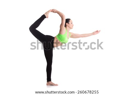 Beautiful sporty girl doing yoga workout, standing in Natarajasana, Lord of the Dance pose, improving balance, asana for stretching shoulders, chest, thighs, groins, abdomen - stock photo