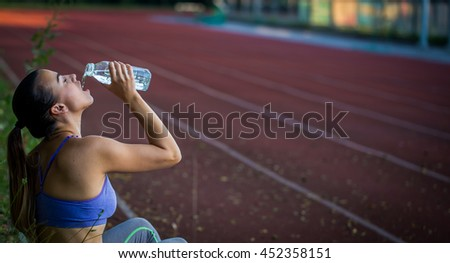 beautiful sporty girl drinking water after running in the stadium, close-up, young sporty woman