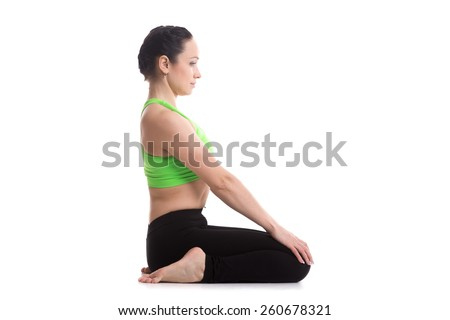 Beautiful sporty girl practices yoga, siting in virasana, hero pose, asana for meditation and pranayama, stretches leg muscles, improves posture