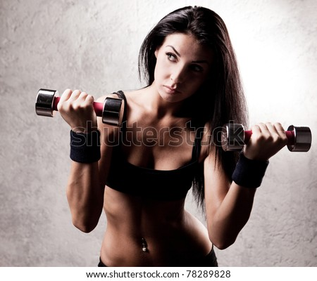 beautiful sporty muscular woman with two dumbbell in the gym