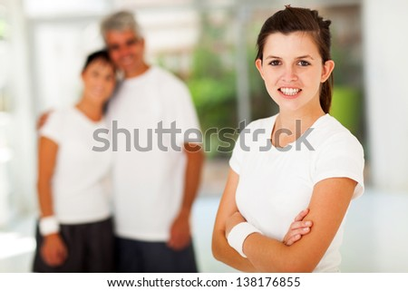 beautiful sporty teen girl in front of parents at home gym - stock photo