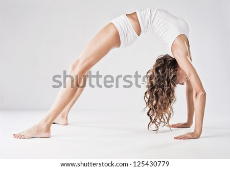 Beautiful sporty woman doing stretching exercise. Backbend. - stock photo