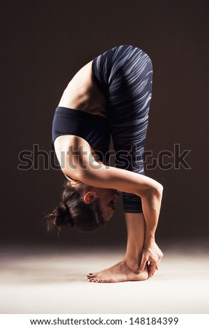 Beautiful sporty woman is working out. Standing forward bend. Uttanasana - stock photo