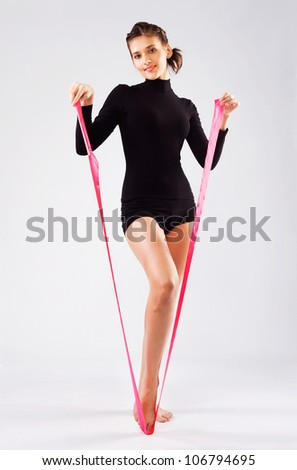 "Beautiful sporty woman making a sign of the letter ""V"" with gymnastic ribbon - stock photo"
