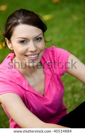 Beautiful sporty woman portrait sitting outdoors smiling - stock photo