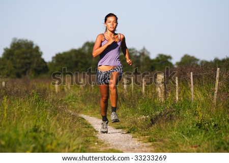 Beautiful sporty woman running on countryside path. Near Randers, Jutland, Denmark. Summer. - stock photo