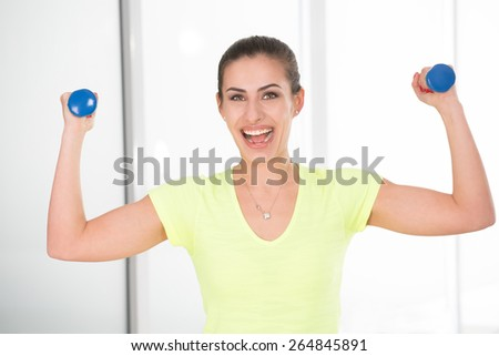 Beautiful sporty woman with dumbbells in gym - stock photo