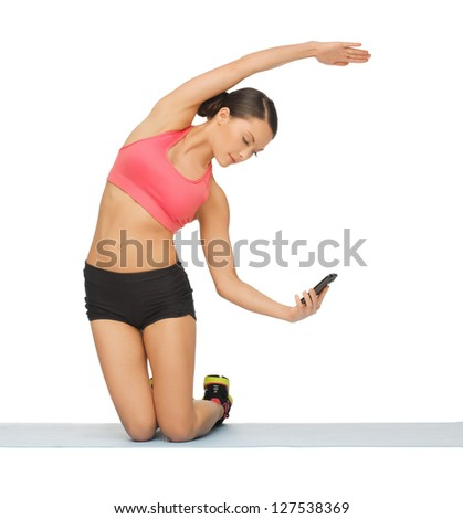 beautiful sporty woman with smartphone doing exercise - stock photo