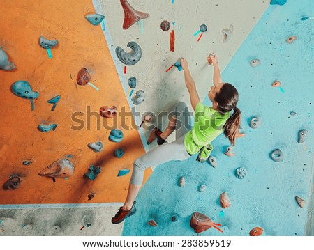 Beautiful sporty young woman climbing on practical wall in gym, bouldering