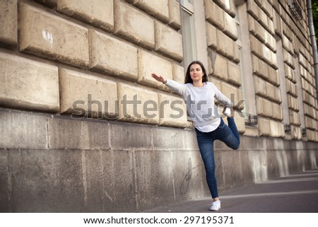 Beautiful sporty young woman working out in front of building wall on city street, standing in easy variation of Natarajasana, Lord of the Dance pose, full length - stock photo
