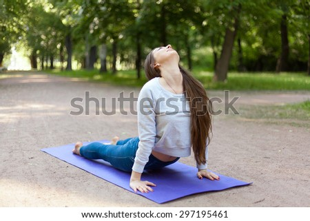 Beautiful sporty young woman working out on street, doing stretching exercises on blue mat in park alley, urdhva mukha shvanasana (upward facing dog pose), sun salutation complex, full length - stock photo