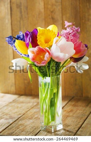 Beautiful spring flowers in glass vase on wooden background - stock photo
