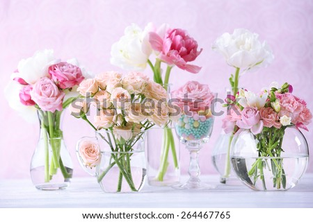 Beautiful spring flowers in glass vases on light pink background - stock photo