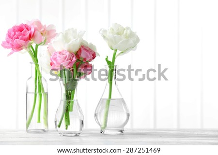 Beautiful spring flowers in glass vases on planks background