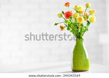 Beautiful spring flowers in vase on window background - stock photo