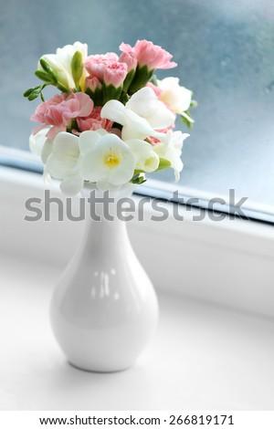 Beautiful spring flowers in vase on windowsill background - stock photo