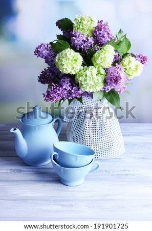 Beautiful spring flowers in vase, on wooden table, on bright background - stock photo