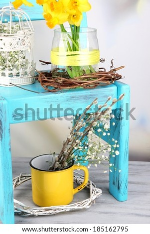 Beautiful spring flowers on blue old wooden chair