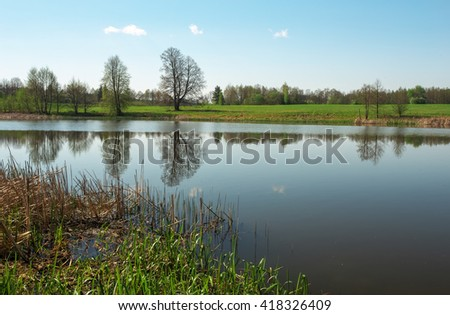 Beautiful spring landscape with river, trees and blue sky. Composition of nature - stock photo