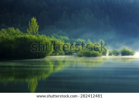 beautiful spring landscape with silent lake reflecting bright green trees. - stock photo