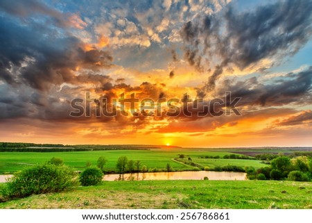 Beautiful spring sunset over pond and plain - stock photo