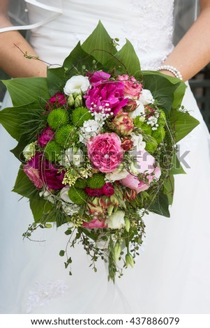 Beautiful spring wedding bouquet - with pink roses and some greens. Natural light. Selective focus.