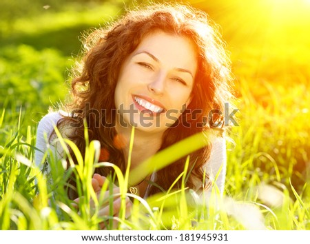 Beautiful Spring Young Woman Outdoors Enjoying Nature. Healthy Smiling Girl in Green Grass. Spring Meadow. Beautiful Lady Lying on the field. Backlit - stock photo